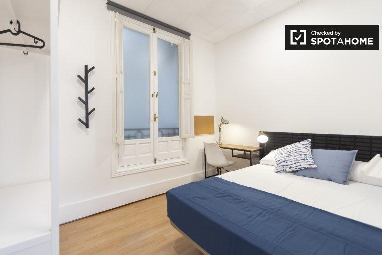 Habitación ordenada en un apartamento de 9 habitaciones en Malasaña, Madrid.