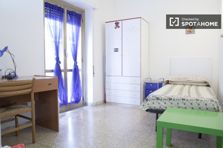 Bedroom 3 with single bed and a balcony.