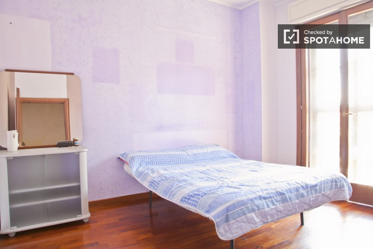 Bedroom 1 with double bed, AC, and balcony