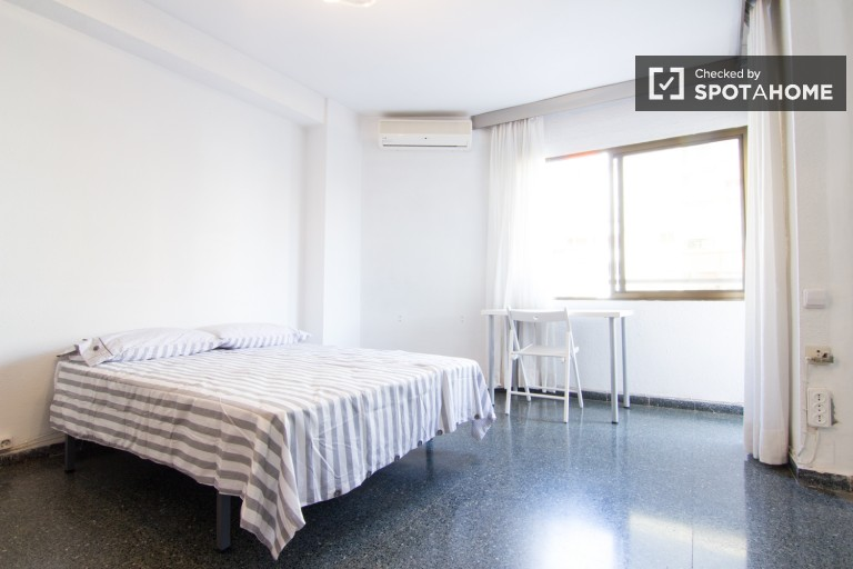 Big room with a double bed and a balcony