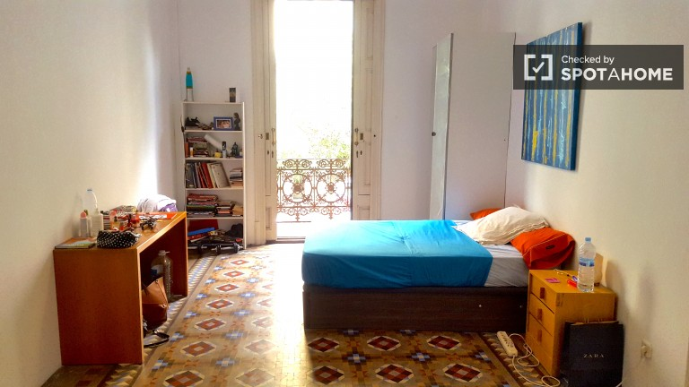 Bedroom 2 with double bed, single bed, and balcony